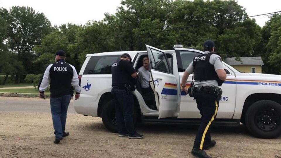 Maxime Bernier dans le siège arrière d'un véhicule de police, entouré de 3 policiers.