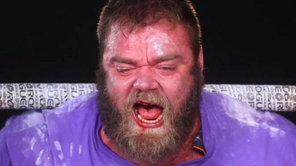 Un homme saigne du nez en forçant.
