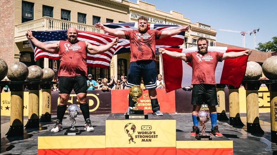 Trois hommes sur un podium.