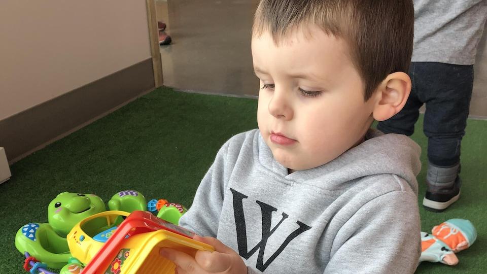 Le jeune Maxime s'amuse avec des jouets.