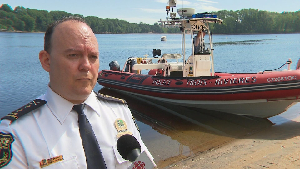 Maxime Gagnon devant un bateau de patrouille de la police de Trois-Rivières.