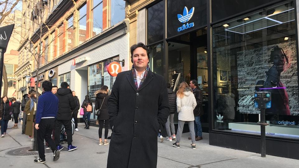 Le président de la Société Saint-Jean-Baptiste, Maxime Laporte, se tient devant la boutique Adidas sur la rue Sainte-Catherine à Montréal. Il y a des gens sur le trottoir et devant la boutique de chaussures.