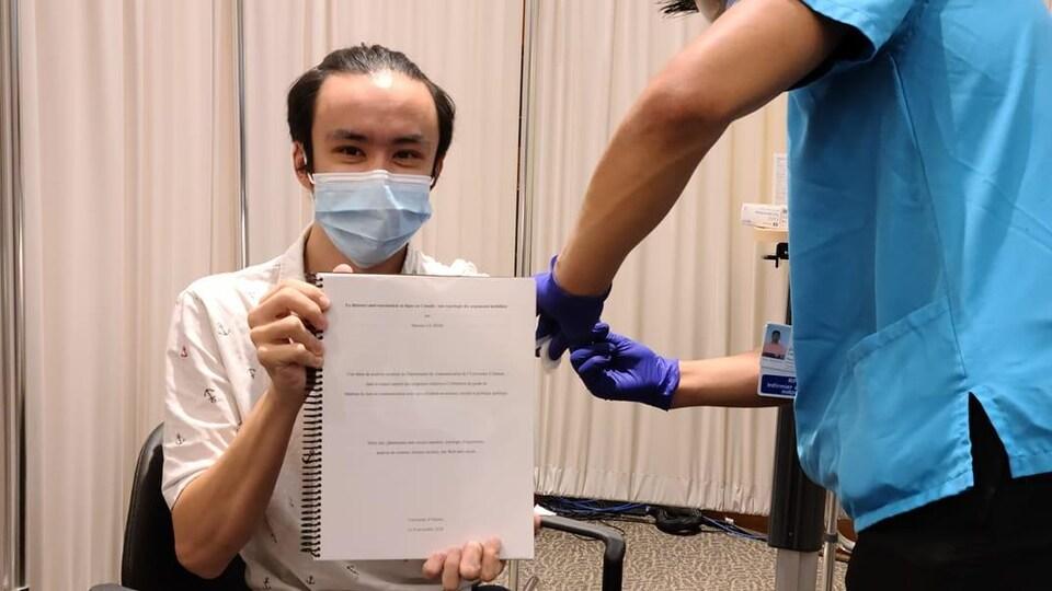 Maxime Lê tient sa thèse tient sa thèse de maîtrise tout en se faisant vacciner.