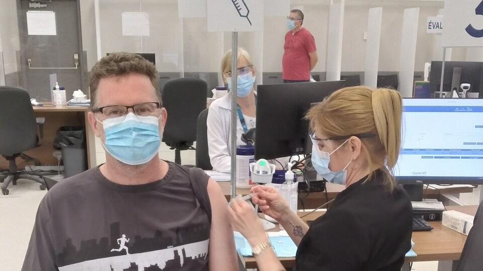 Une infirmière vaccine le maire de Gatineau Maxime Pedneaud-Jobin.