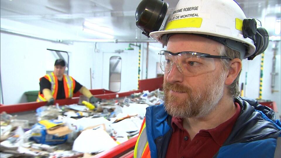 Un homme qui porte un casque et des lunettes de protection répond aux questions d'un journaliste.