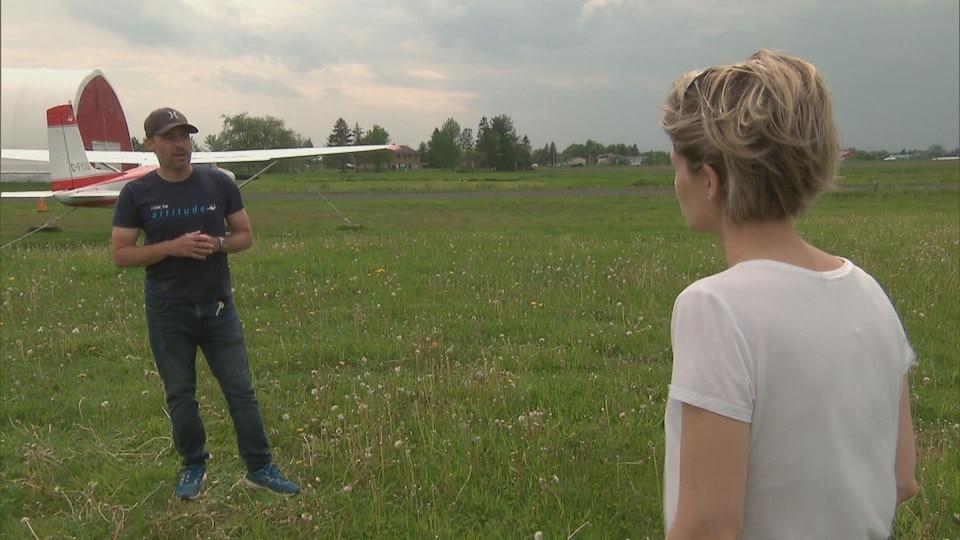 Un homme debout devant un avion dans un champ.