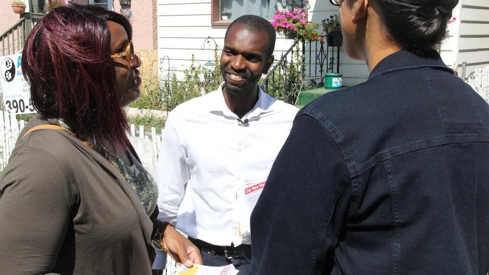 Trois personnes discutent dans la rue.