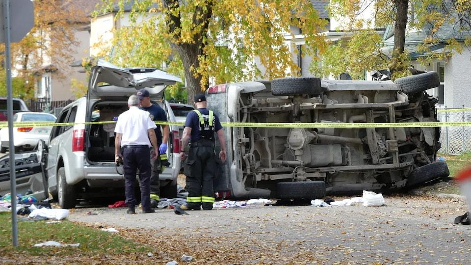 Des policiers observent un camion renversé et une camionnette endommagée dans une rue bordée par des arbres, le 26 septembre 2020.