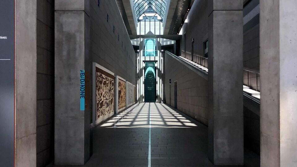 Un grand hall de pierre au plafond vitré avec, au sol, des flèches directionnelles.