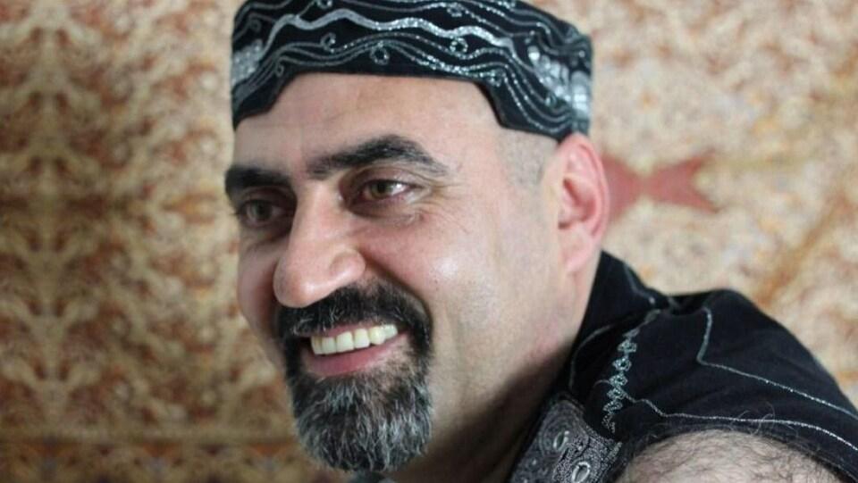 Photo d'un homme avec une barbichette, portant un petit chapeau.