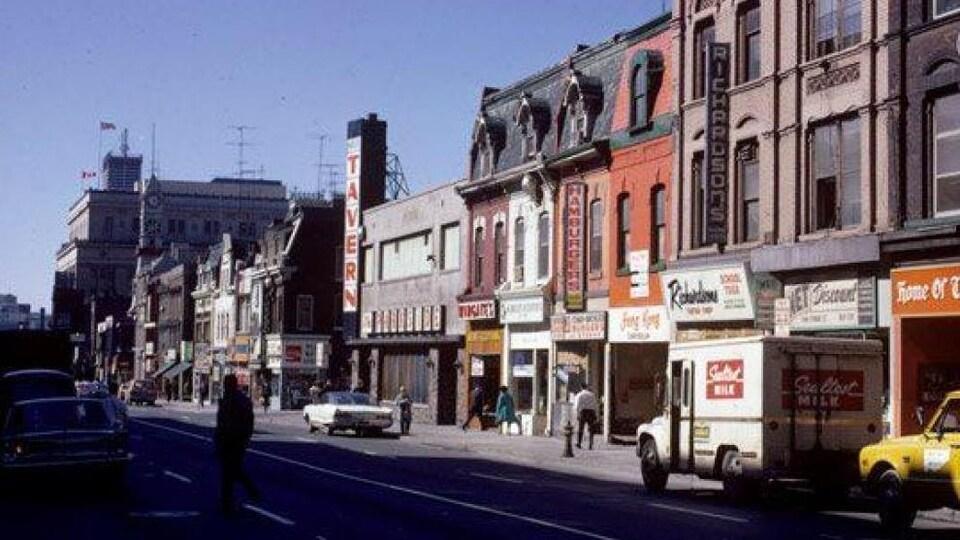 Photo de la rue Yonge dans les années 1970 avec de vieilles voitures garées le long de la rue.