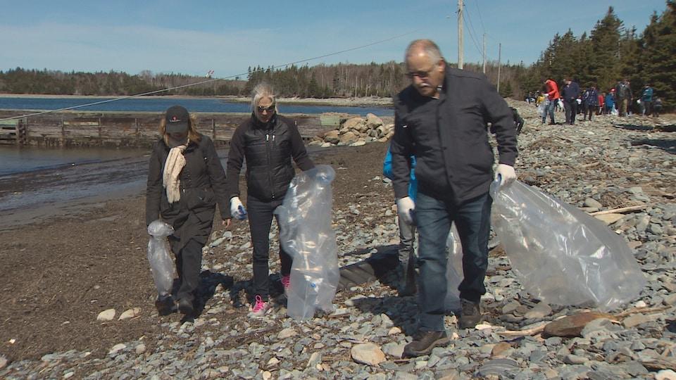 Catherine McKenna marche sur la plage avec d'autres gens en déposant des déchets dans de grands sacs