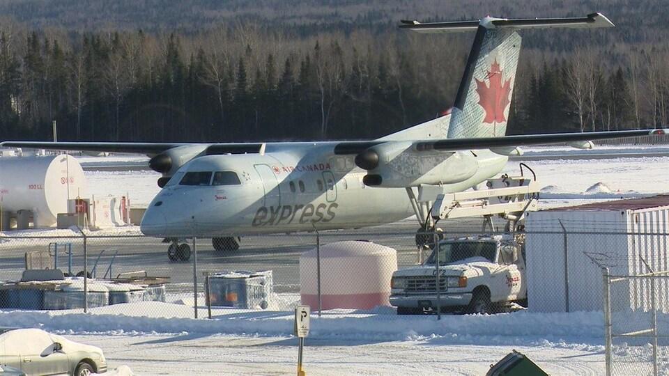 Un avion d'Air Canada Express à un aéroport enneigé.