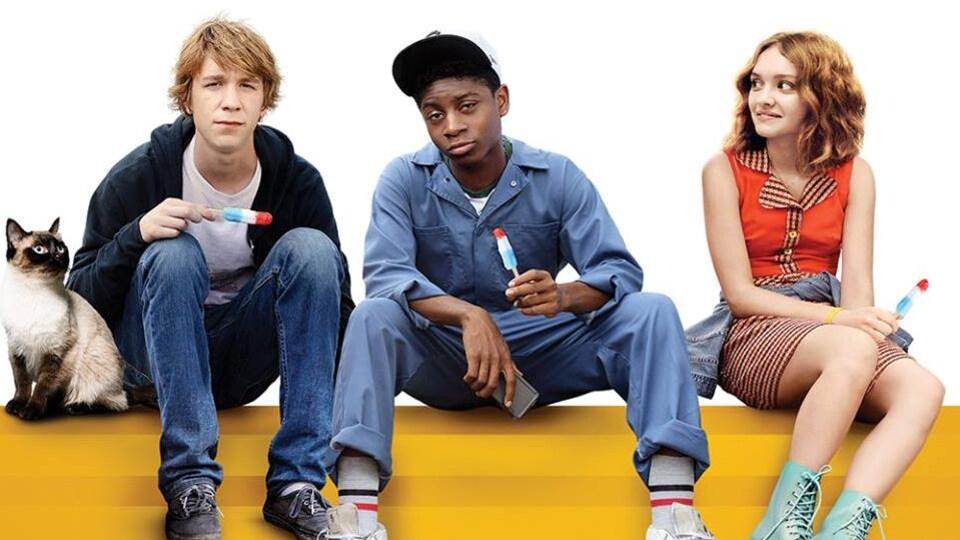 Trois adolescents mangent des sucettes glacées, assis.