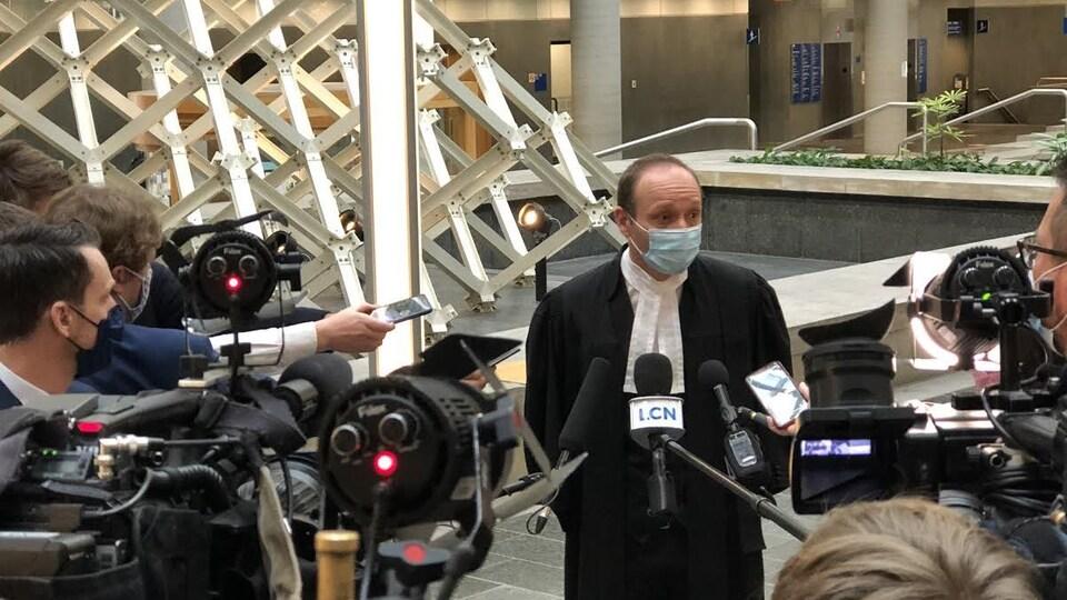 Me François Godin lors d'une mêlée de presse avec des micros.