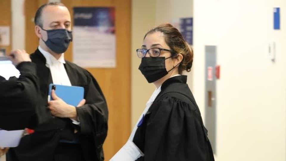 Les deux avocats se trouvent devant la porte de la salle d'audience.