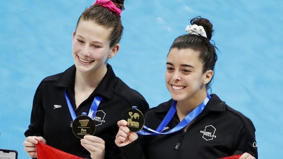 Les deux femmes, souriantes, montrent fièrement leur médaille et tiennent un drapeau canadien.