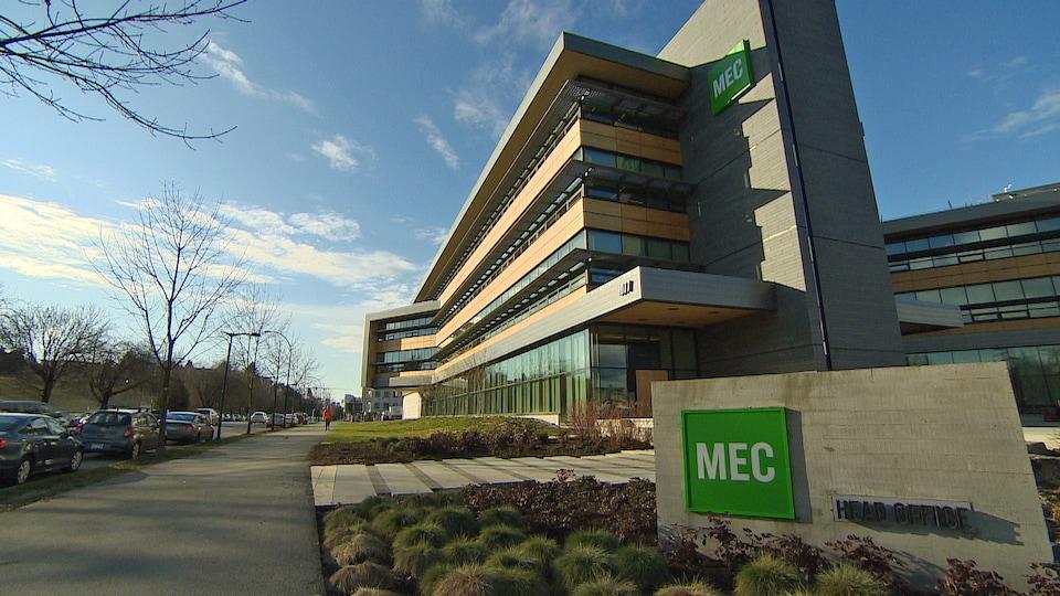 Le siège principal de l'entreprise MEC. Un immeuble gris avec beaucoup de fenêtres situé au bord d'une rue et d'un sentier pour piétons et cyclistes.