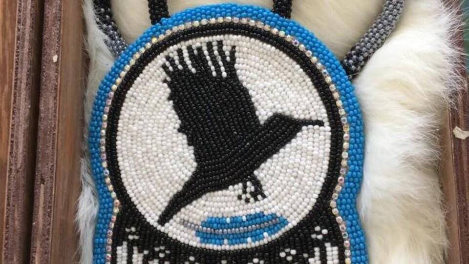Un médaillon autochtone orné d'un oiseau noir