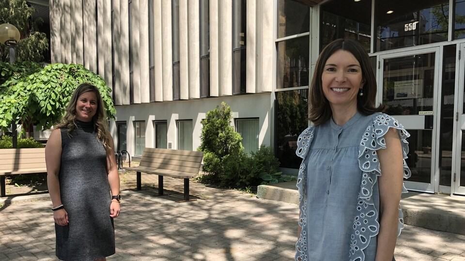 Les deux femmes debout dehors devant un bâtiment.