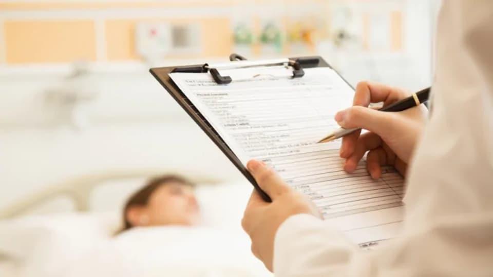 Un médecin écrit des notes dans le dossier médical d'un patient.