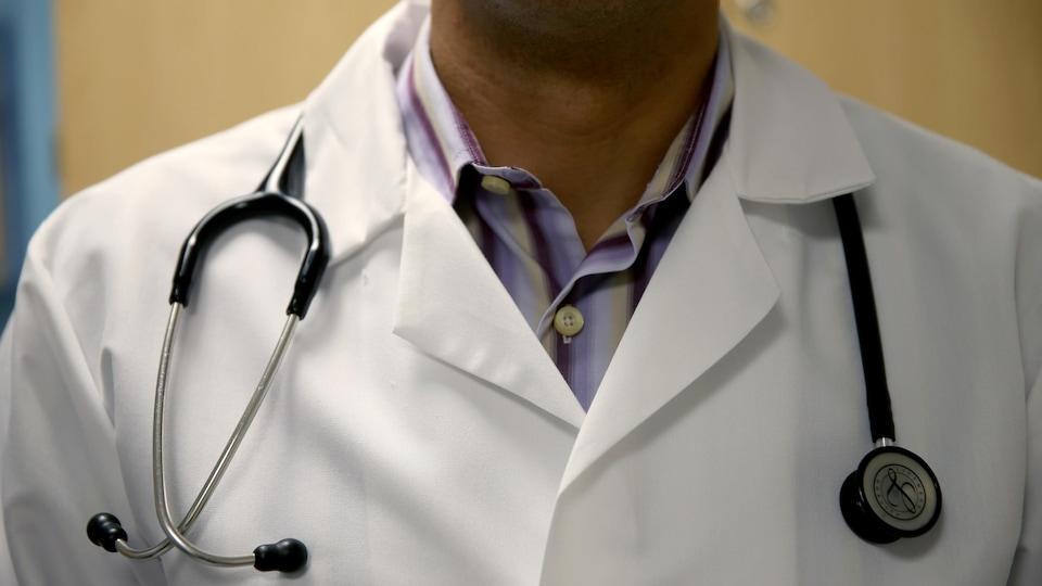 Un médecin vêtu de son sarrau, avec un stétoscope lui tombant sur les épaules.