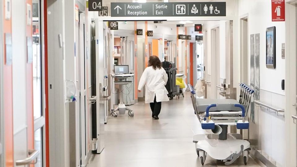 Une femme habillée avec un sarrau blanc marche dans un corridor d'hôpital où l'on voit une civière.