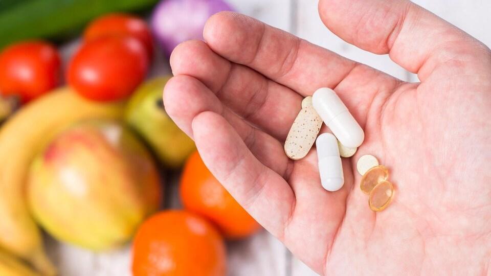 Plusieurs pilules dans le creux d'une main au-dessus de plusieurs fruits et légumes.