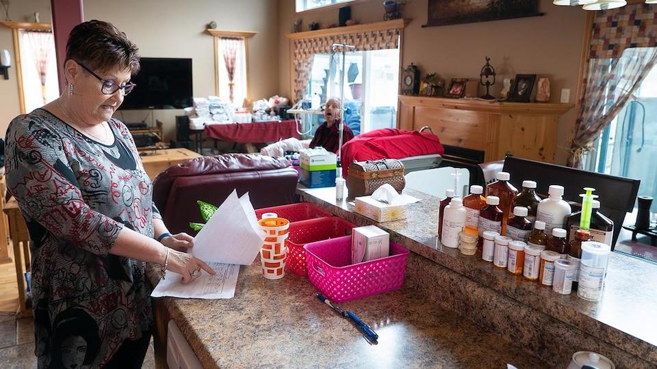 On voit Mme Desjardins près du comptoir de la cuisine sur lequel sont posées de nombreuses bouteilles de médicaments. Elle consulte une feuille. En arrière-plan, son mari, Maurice, assis, qui l'observe.
