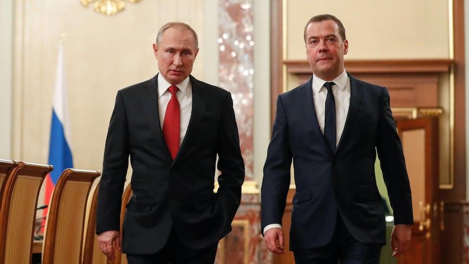Vladimir Poutine et Dimitri Medvedev marchent dans une salle de réception du Kremlin à Moscou.
