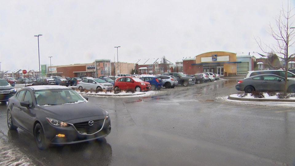 Plusieurs voitures dans un stationnement entouré de magasins.