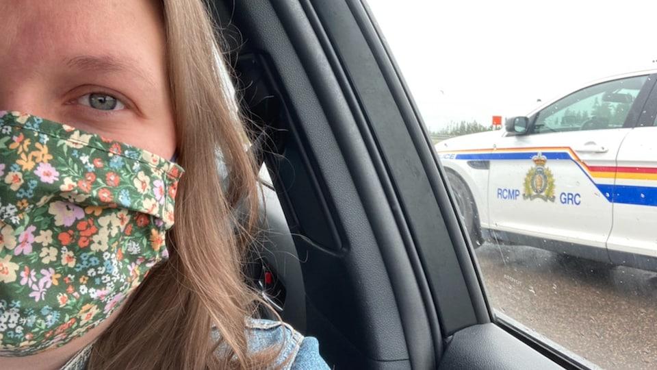 Megan Mitton dans une voiture, un véhicule de la GRC en arrière-plan.