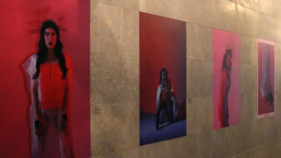 Des œuvres d'art visuel représentant des femmes sur un fond rouge sont affichées.