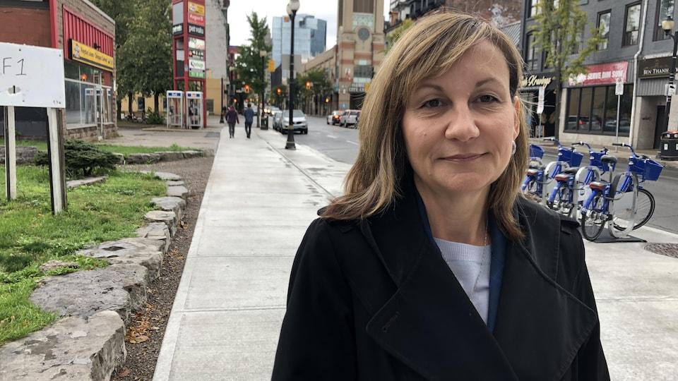 Une femme dans un manteau regarde la caméra, rue James, à Hamilton.
