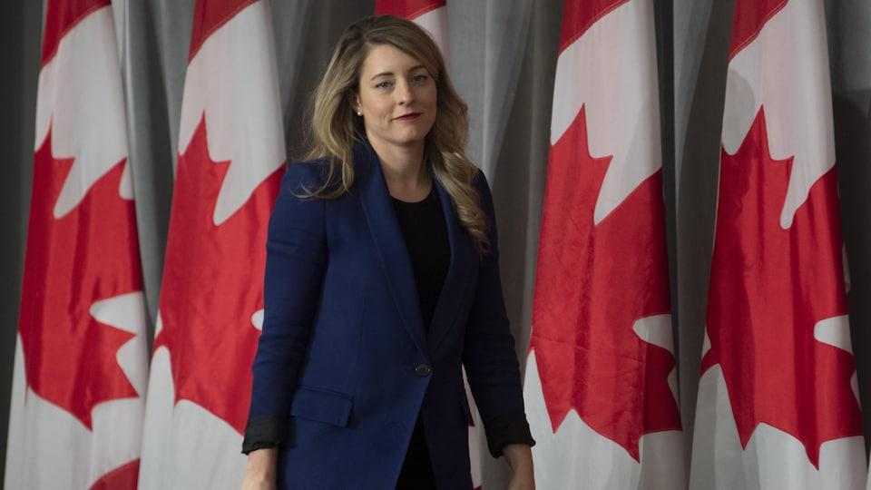 Elle marche devant des drapeaux canadiens.