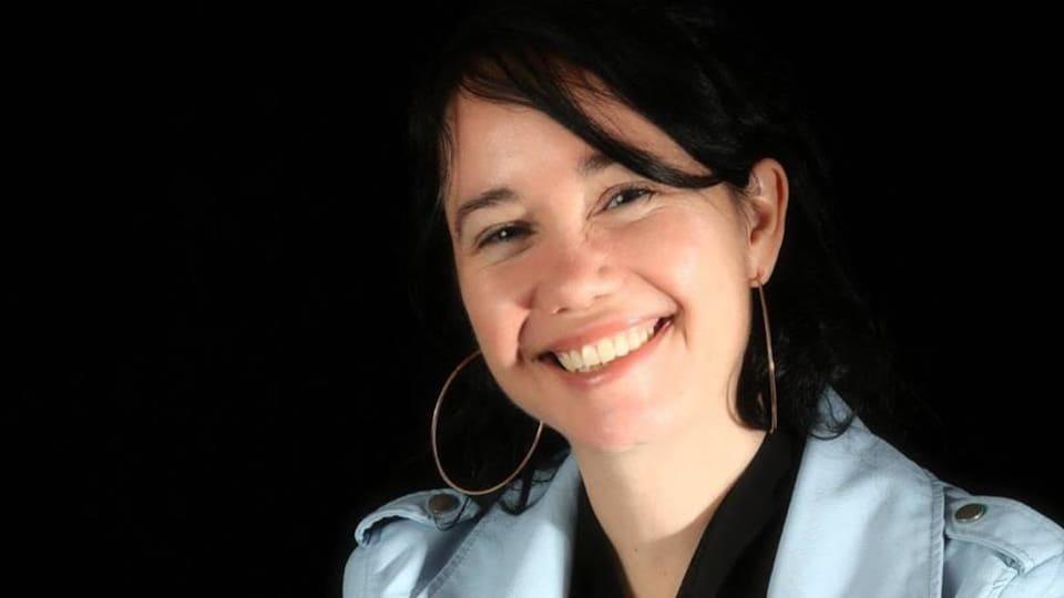Une femme aux cheveux foncés sourit.