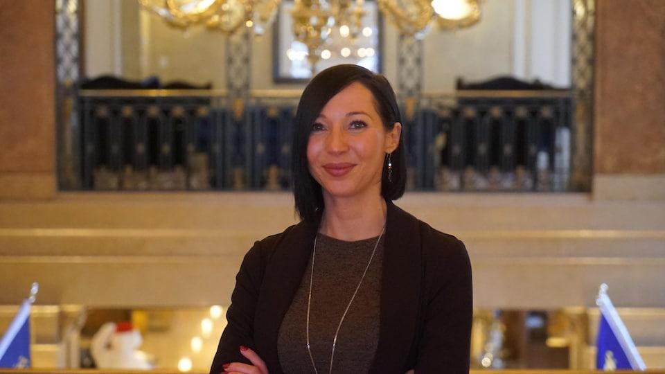 Une femme sourit, les bras croisés, devant un chandelier suspendu.