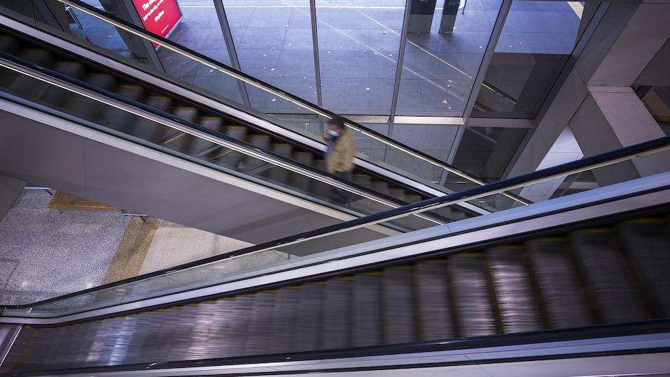Un homme portant un masque sur un escalier mécanique.