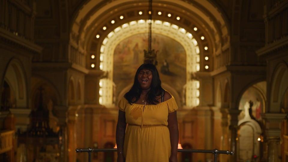 Une femme vêtue d'une robe jaune chante dans une église.