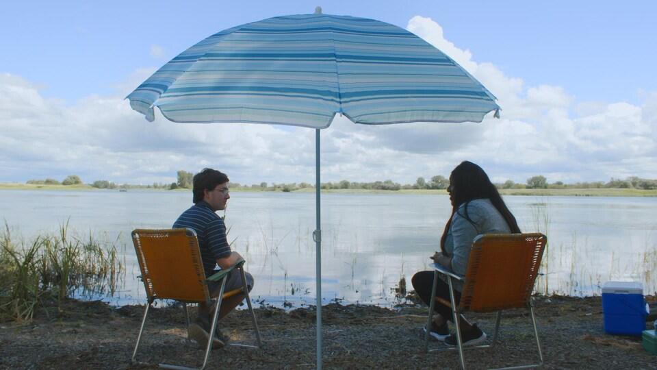 Mélissa Bédard et un jeune homme sont assis sous un parasol.