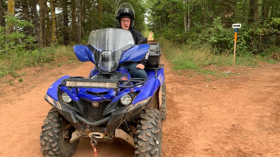 Peter Mellish interviewé sur son véhicule le long d'une piste en forêt.