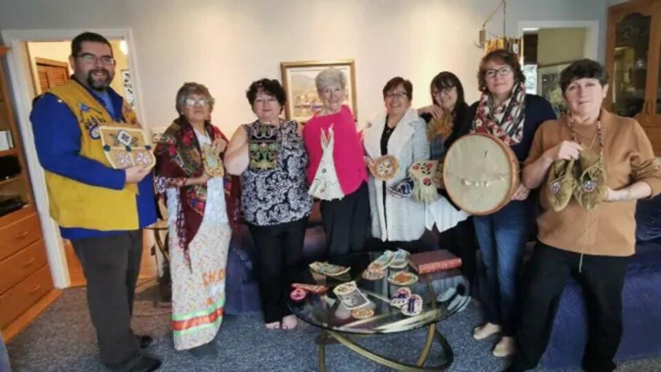 Un homme et sept femmes posent avec des artefacts autochtones dans les mains.