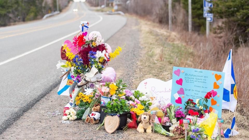 Des fleurs, des bouquets, des animaux en peluche et un message personnalisé déposés sur le bord d'une route.