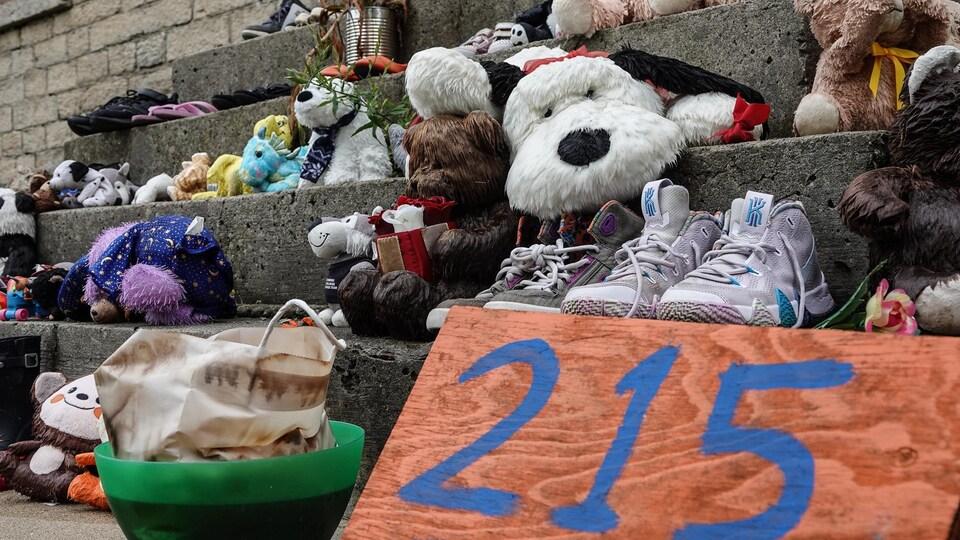 Des souliers et des jouets d'enfants sont disposés sur des marches et on peut lire le nombre 215 sur une affiche.