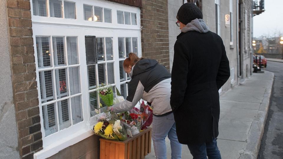 Une femme dépose un bouquet de fleurs devant la résidence, tandis que son conjoint regarde la scène et se recueille.