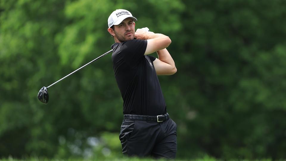 Le golfeur en plein élan regarde sa balle s'envoler.