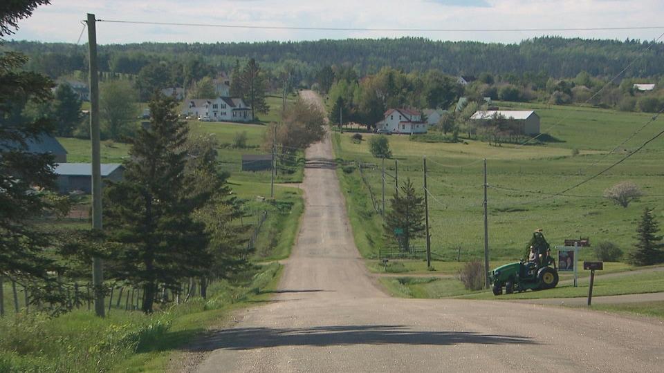 Des terres agricoles bordent la route de campagne. Un homme à bord d'un tracteur tond sa pelouse.