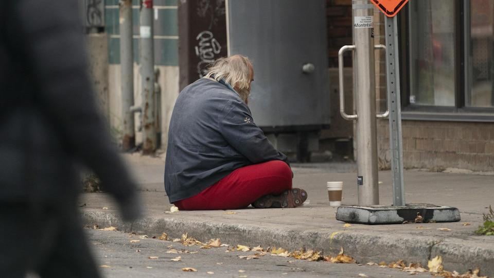 Un mendiant assis sur un trottoir.