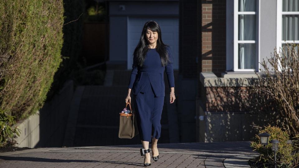 Meng Wanzhou marche devant son domicile à Vancouver.
