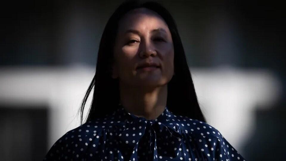 Meng Wanzhou, le visage partiellement couvert par une ombre.